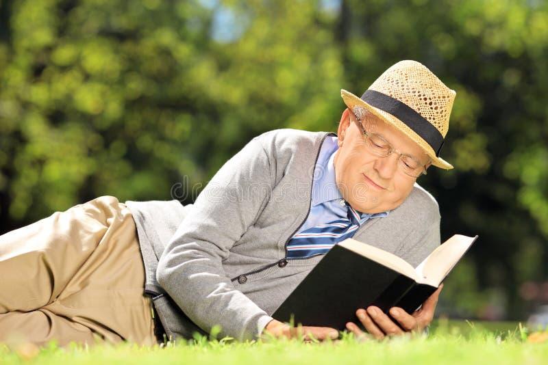 Hög man med hatten som ligger på ett gräs och en läsning en bok i en medeltal royaltyfri foto