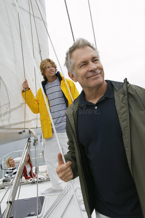 Hög man med sonen på yachten fotografering för bildbyråer