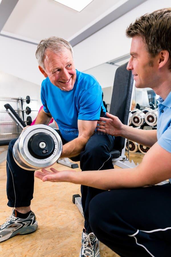 Hög man och instruktör på övningen i idrottshall arkivfoton