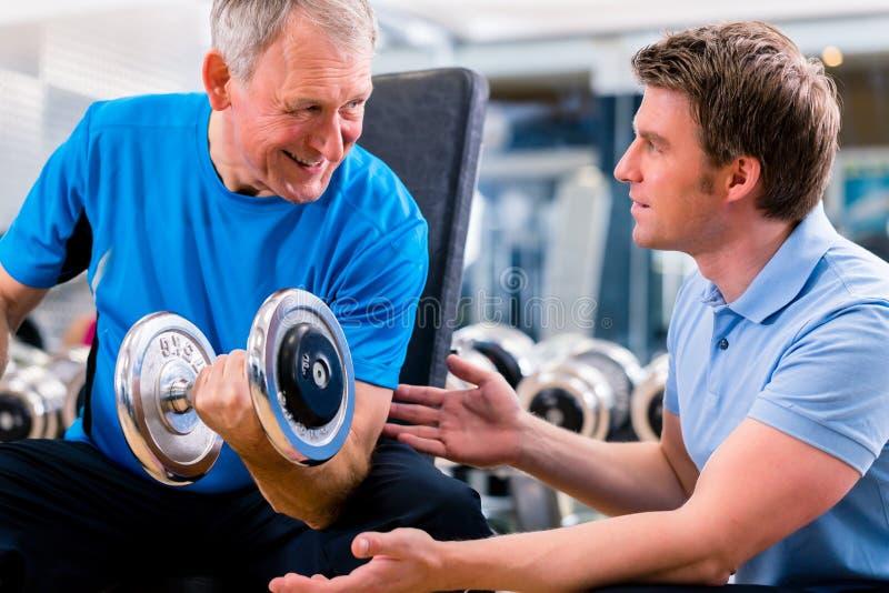 Hög man och instruktör på övningen i idrottshall royaltyfria bilder