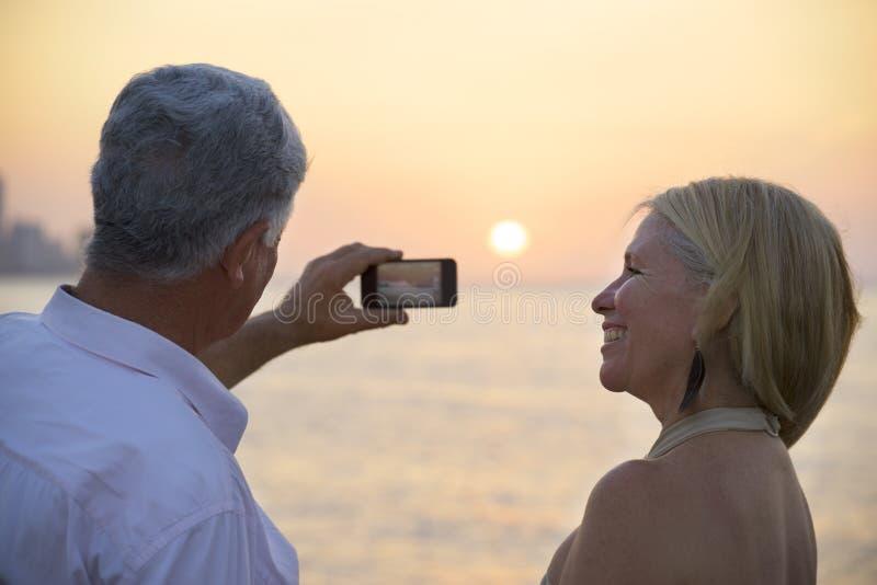 Hög man och kvinna som använder mobiltelefonen för att ta fotoet royaltyfria bilder