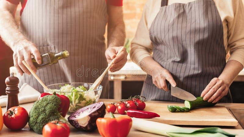 Hög man och kvinna som lagar mat grönsaksallad på kök royaltyfri bild