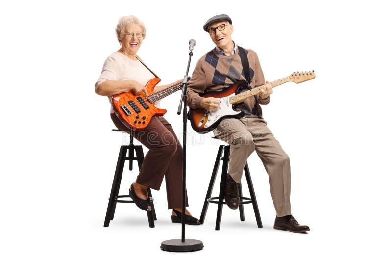 Hög man och kvinna som sitter och spelar elektriska gitarrer arkivfoto