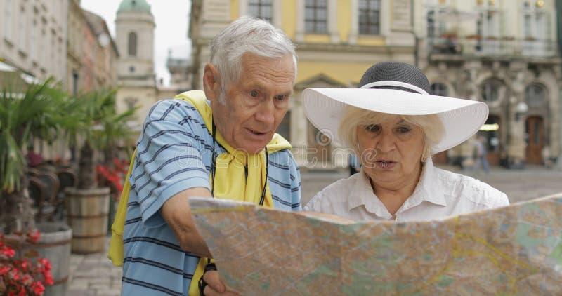 Hög man och kvinnliga turister som står med en översikt i händer som söker efter rutten royaltyfria bilder