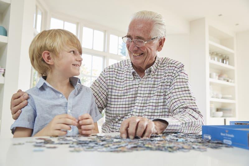 Hög man och sonson som hemma gör ett pussel royaltyfri fotografi