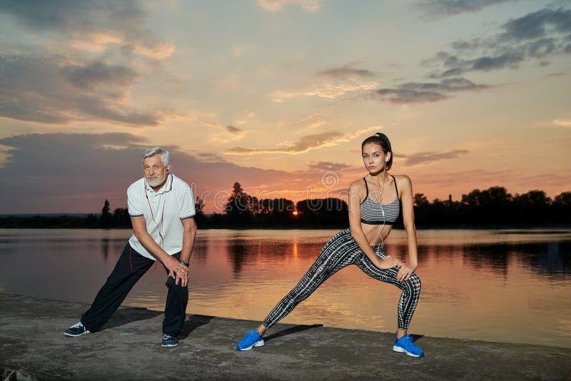 Hög man och ung flicka som har sporten som utbildar nära sjön på solnedgång royaltyfri foto