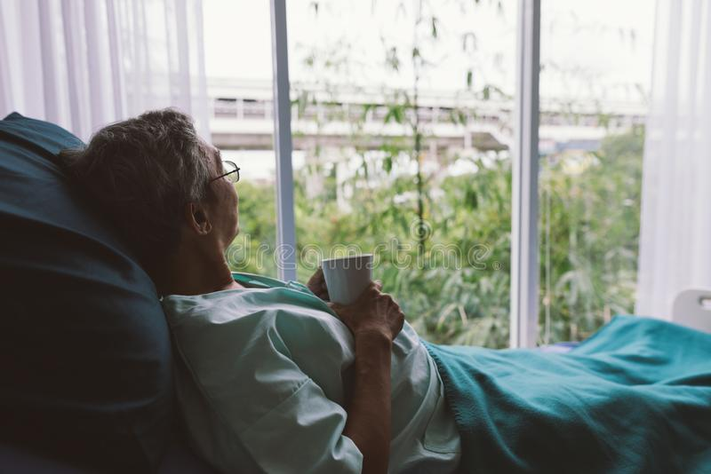 Hög man på en sjukhussäng bara i ett rum som ser till och med sjukhusfönstret gammalare t?lmodig royaltyfri fotografi