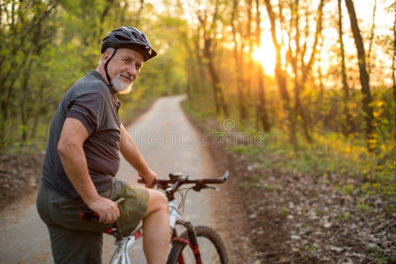 Hög man på hans mountainbike utomhus fotografering för bildbyråer