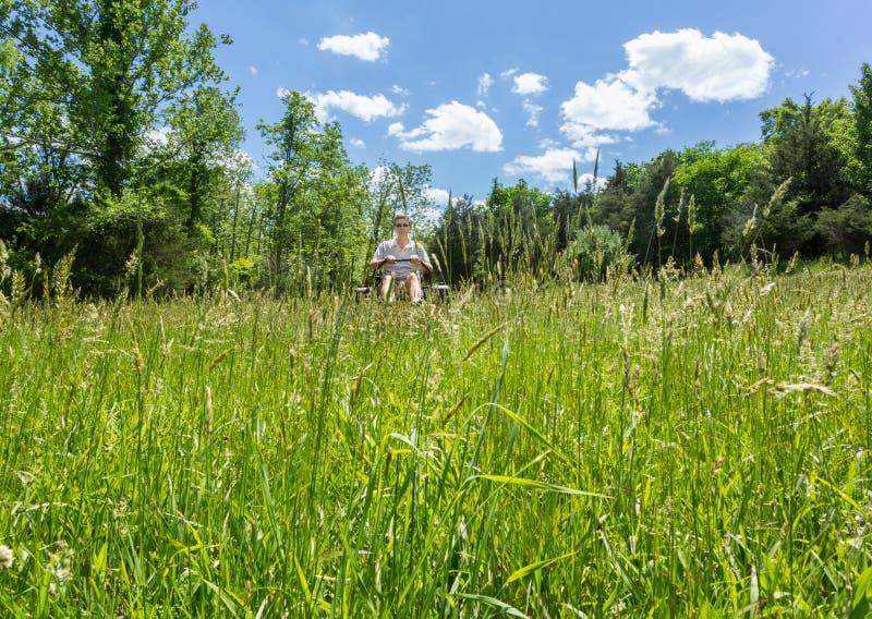 Hög man på nollvändgräsklipparen i äng royaltyfria foton