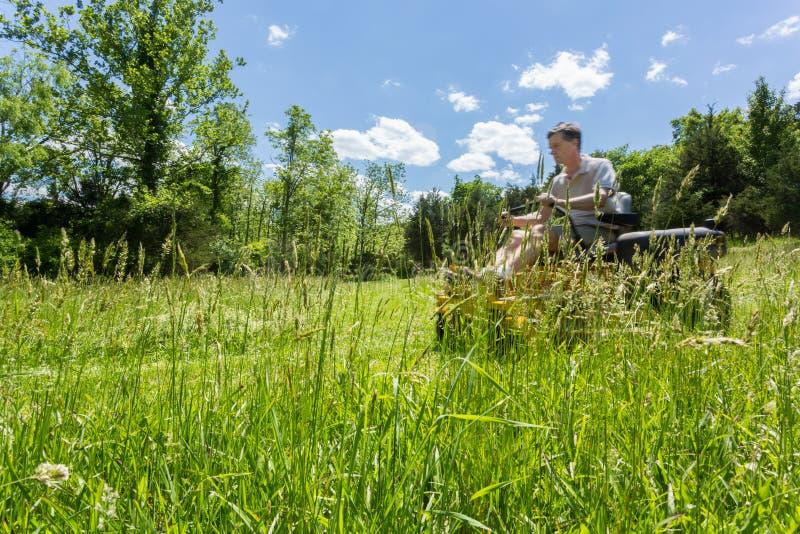 Hög man på nollvändgräsklipparen i äng royaltyfria bilder