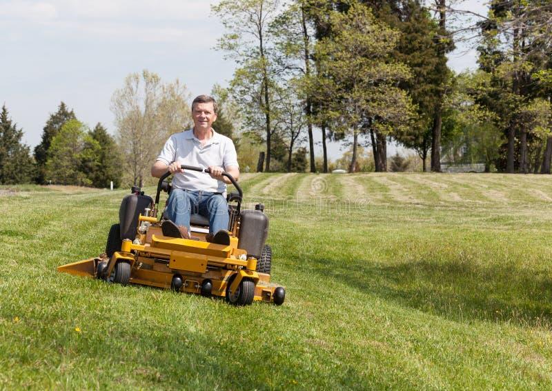 Hög man på nollvändlawngräsklippningsmaskinen på torva royaltyfri fotografi