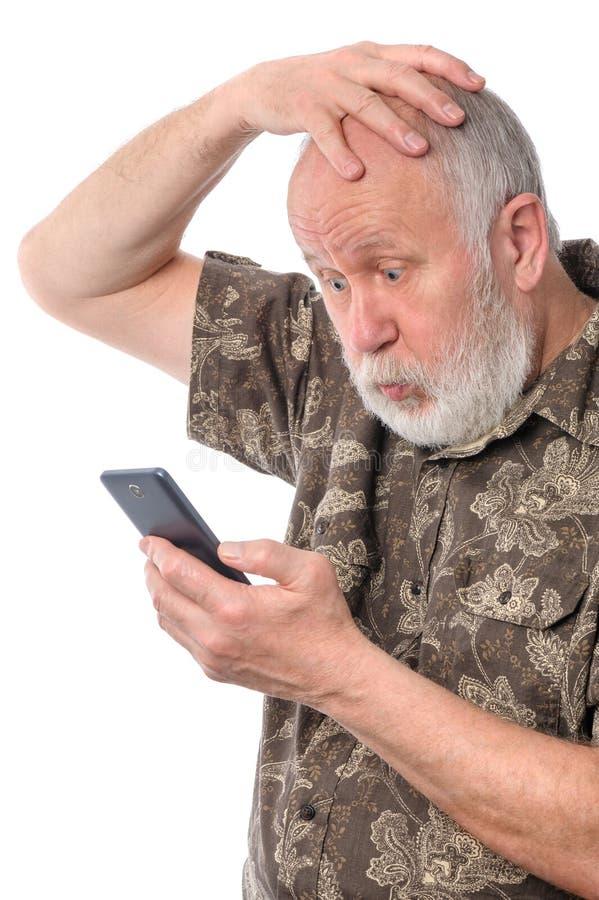 Hög man som är förvirrad med något på den mobila smartphonen som isoleras på vit arkivfoto