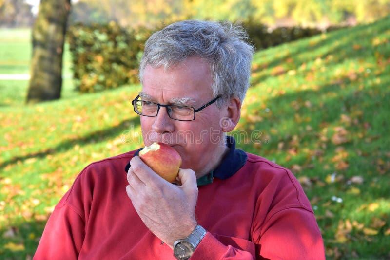 Hög man som äter äpplet royaltyfri foto