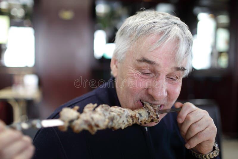 Hög man som äter kebab på en pinne royaltyfria bilder