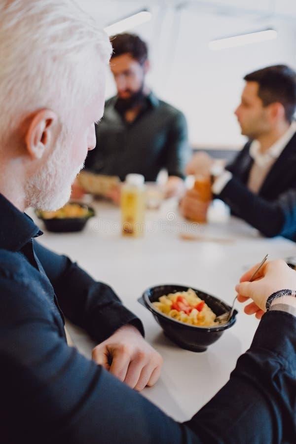 Hög man som äter pasta i kontorskafeterian arkivfoto