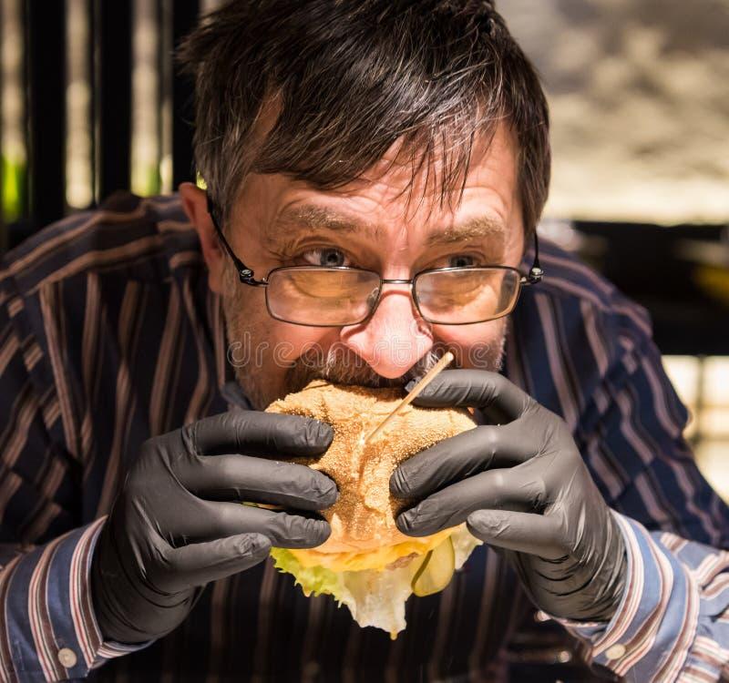 Hög man som äter smakliga burgerinsvarthandskar arkivfoton