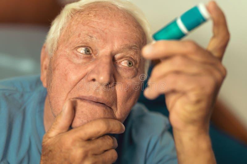 Hög man som använder ögondroppar royaltyfri bild