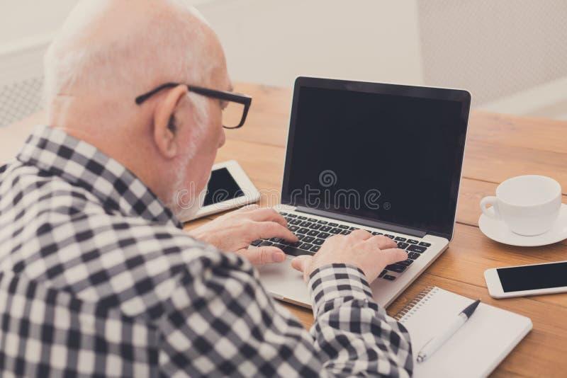 Hög man som använder bärbara datorn med modellen för tom skärm royaltyfri bild