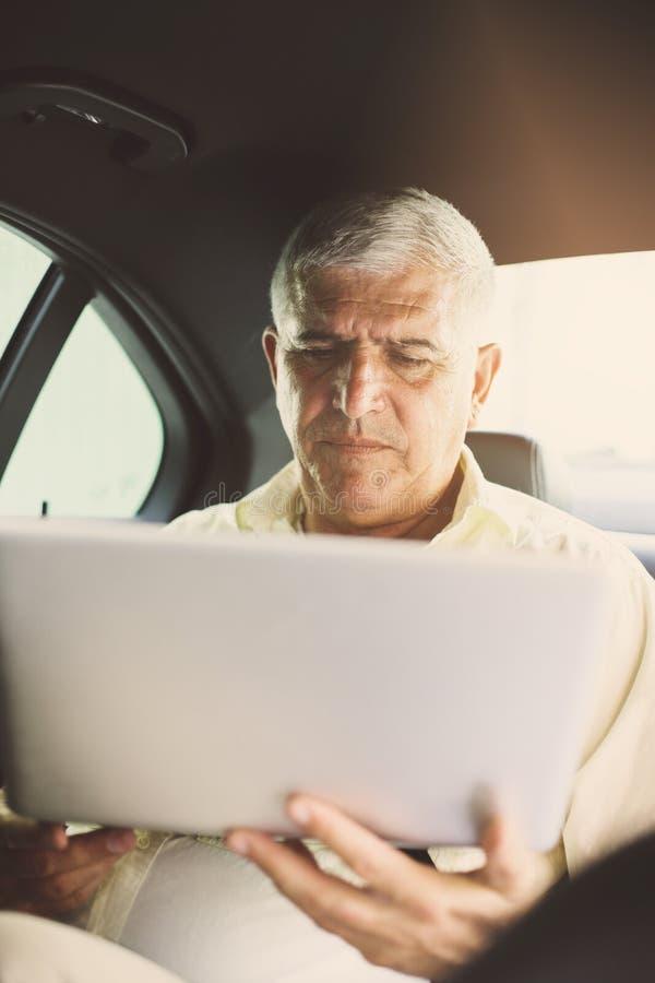Hög man som använder datoren i taxi royaltyfri fotografi