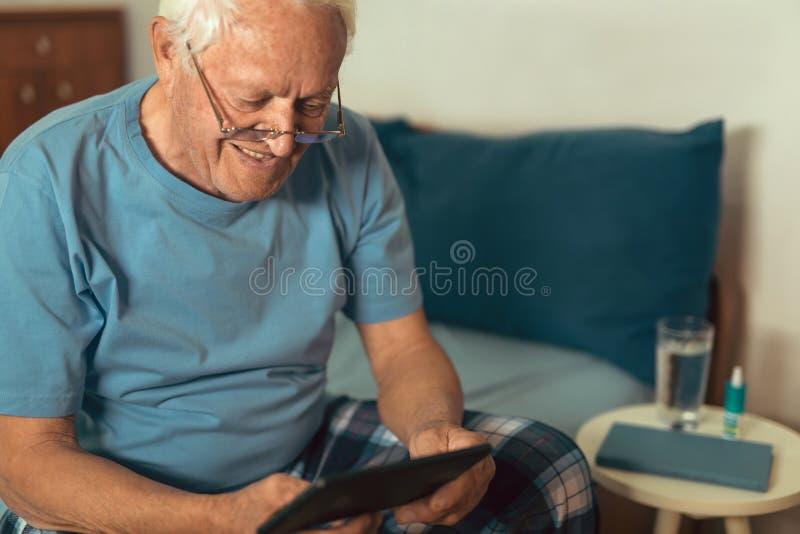 Hög man som använder den digitala minnestavlan royaltyfria bilder