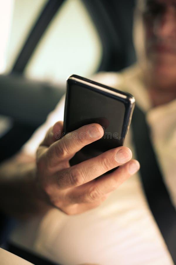 Hög man som använder den smarta telefonen i taxi royaltyfri bild