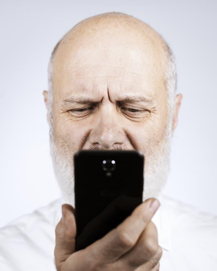 Hög man som använder en telefon och har synförmågaproblem royaltyfria foton