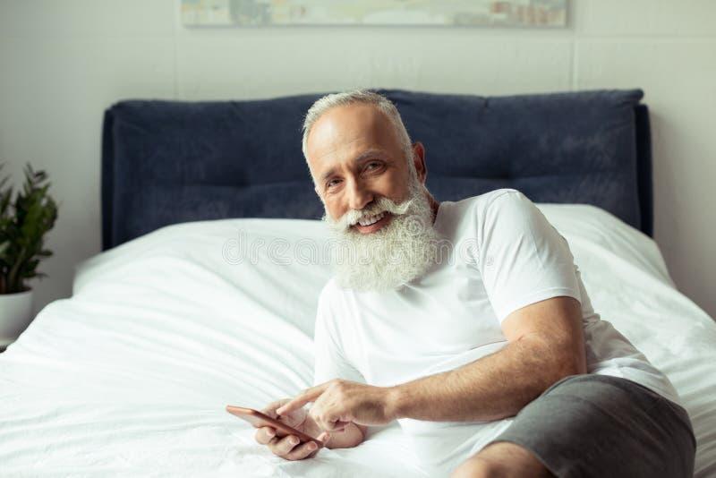 Hög man som använder smartphonen, medan ligga på säng royaltyfri foto
