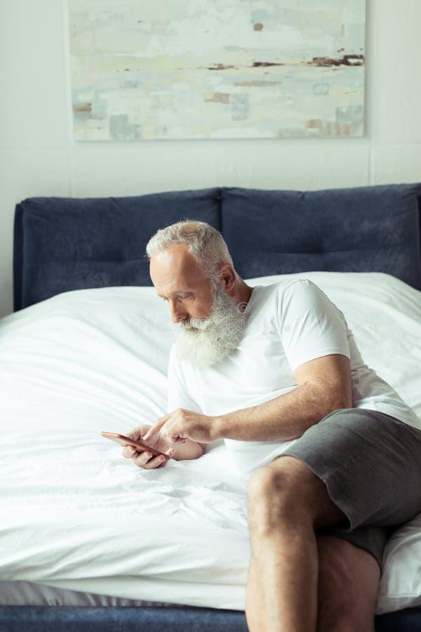 Hög man som använder smartphonen, medan ligga på säng royaltyfri fotografi