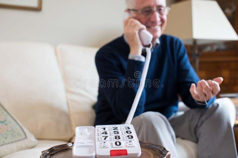 Hög man som använder telefonen med det hemmastadda överdimensionerade tangentbordet fotografering för bildbyråer