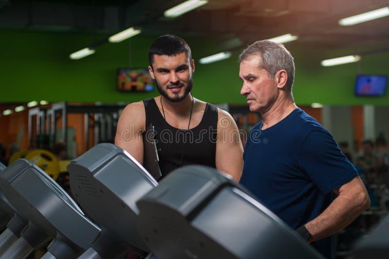 Hög man som arbetar med den personliga instruktören i idrottshall arkivbilder
