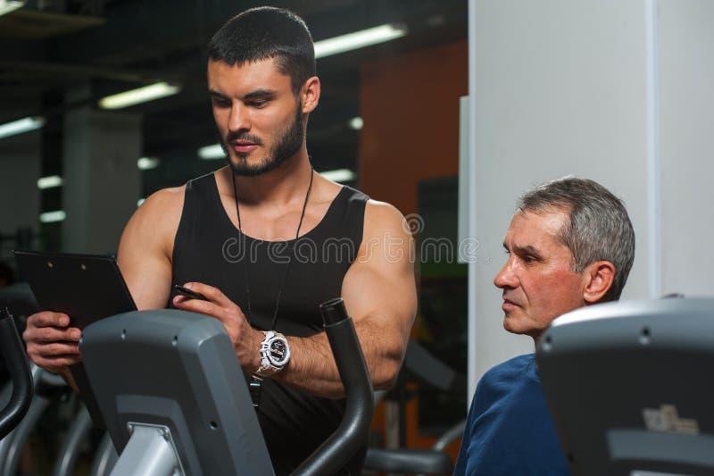 Hög man som arbetar med den personliga instruktören i idrottshall royaltyfri foto