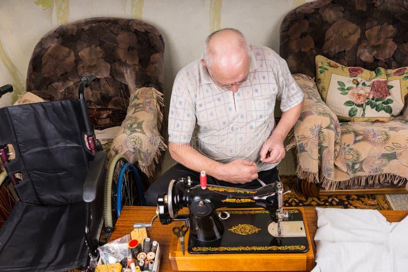 Hög man som arbetar på den gammalmodiga symaskinen royaltyfri fotografi
