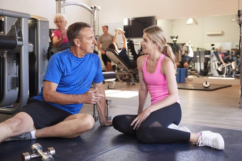 Hög man som diskuterar övningsprogram med den manliga personliga instruktören In Gym arkivbilder