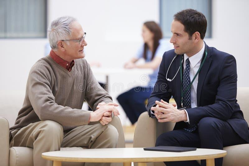 Hög man som diskuterar provresultat med doktorn arkivfoton