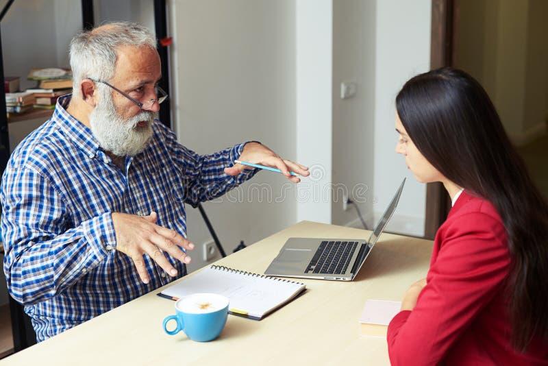 Hög man som förklarar något till den unga kvinnan i hans kontor fotografering för bildbyråer