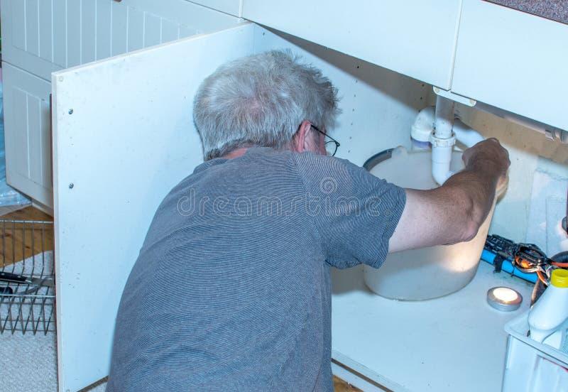 Hög man som fixar ett läcka rör under vasken arkivfoto