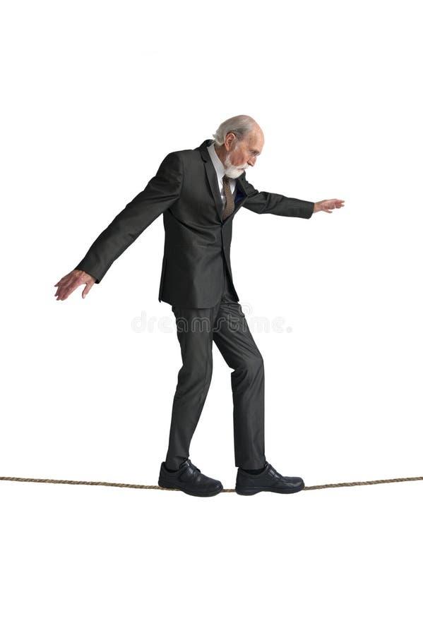 Hög man som går en spänd lina arkivfoton
