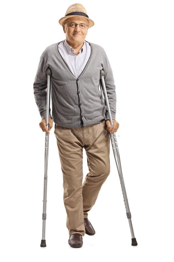 Hög man som går med kryckor och ler på kameran fotografering för bildbyråer