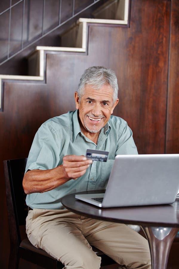 Hög man som gör online-shopping med kreditkorten arkivbilder