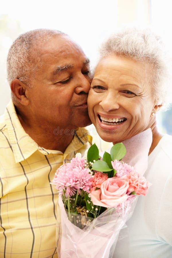 Hög man som ger blommor till frun royaltyfri foto