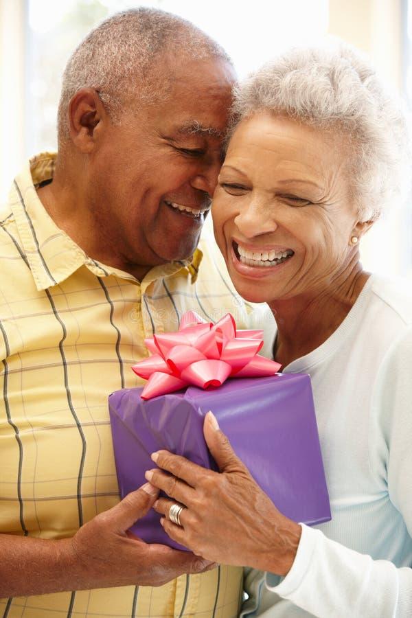 Hög man som ger gåvan till frun arkivfoton