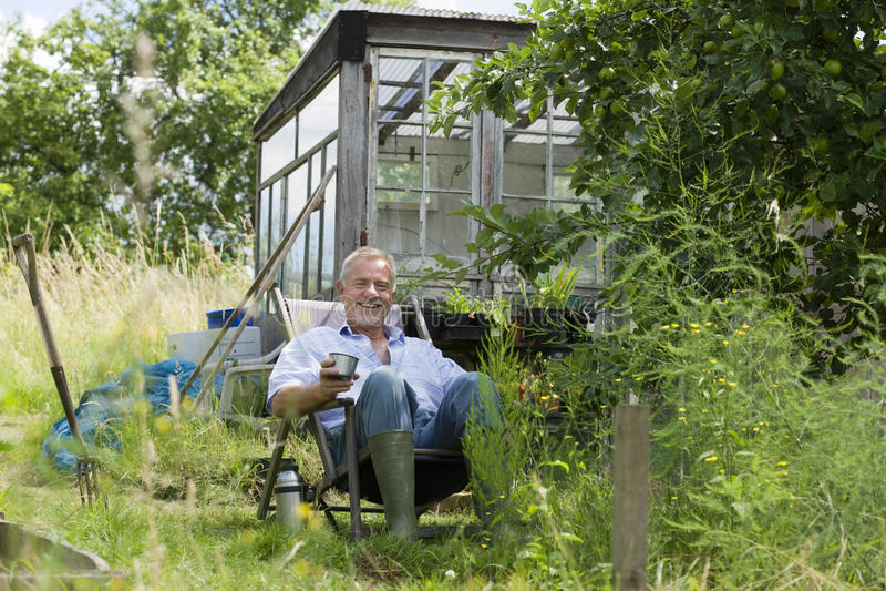 Hög man som har drinken, medan sitta i trädgård arkivbild