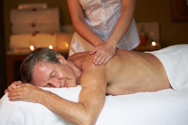 Hög man som har massage i Spa royaltyfria bilder