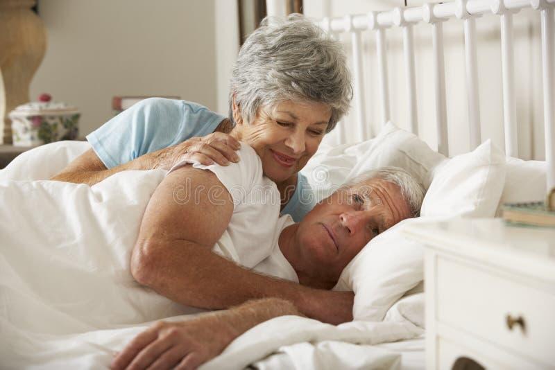 Hög man som har svårighet, i att sova i säng med frun royaltyfri foto