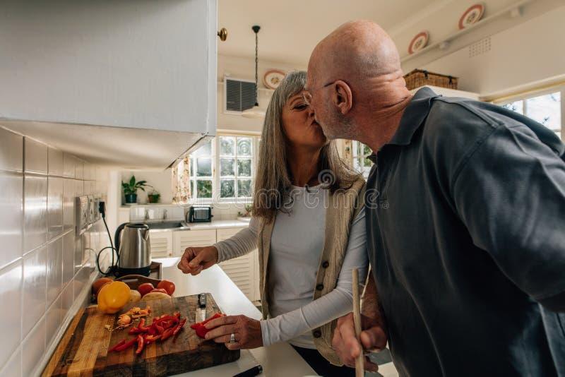 Hög man som hemma kysser hans fruanseende i kök Man och kvinna som har roligt, medan laga mat tillsammans i kök royaltyfri bild