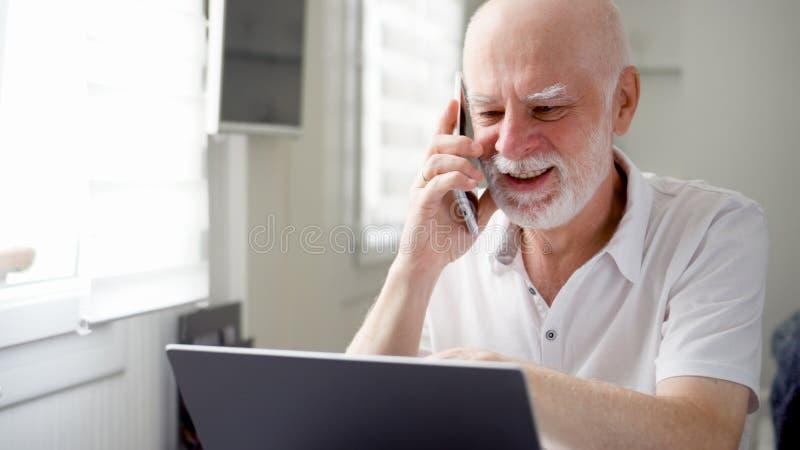 Hög man som hemma sitter med bärbara datorn och smartphonen Använda mobiltelefonen som diskuterar projekt på skärmen royaltyfri bild