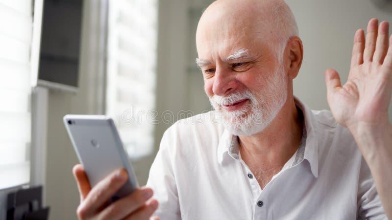 Hög man som hemma sitter med smartphonen Använda mobilen som talar via budbäraren app Le den vinkande handen i hälsning royaltyfri foto