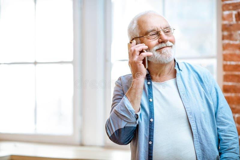 Hög man som hemma talar med telefonen royaltyfri fotografi