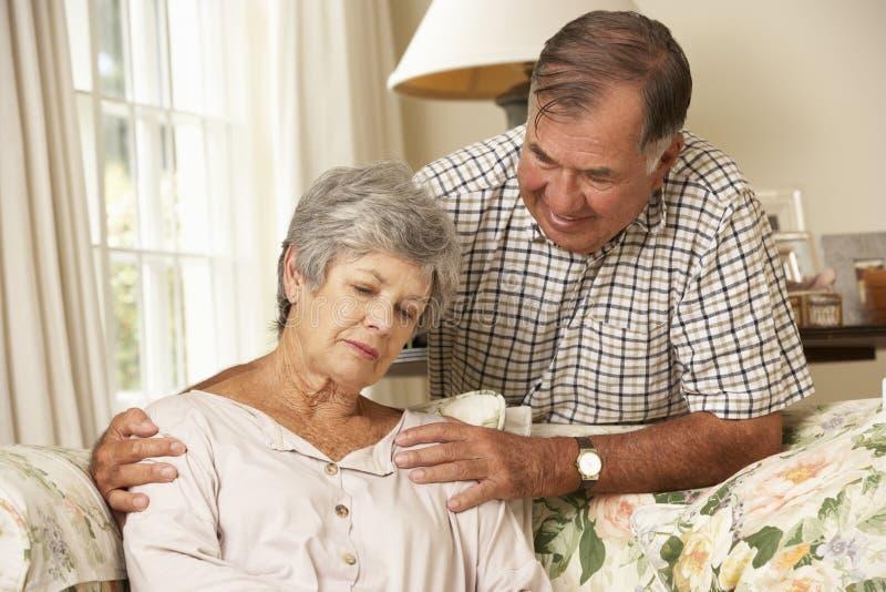 Hög man som hemma tröstar den olyckliga frun arkivbild