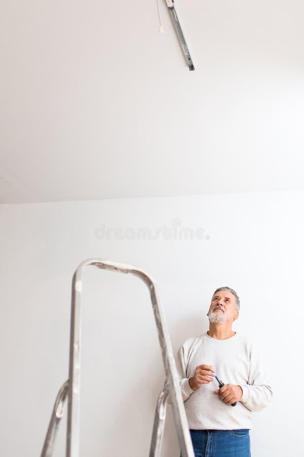 Hög man som installerar ett takljus i lägenhet arkivbild